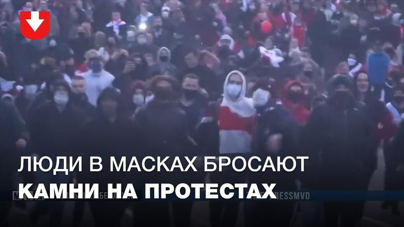 Люди в масках бросают камни во время протестного марша в воскресенье