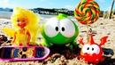 Om Nom e o pequeno dragão brincam na praia. OmNom de brinquedo. Vídeos de brinquedos.